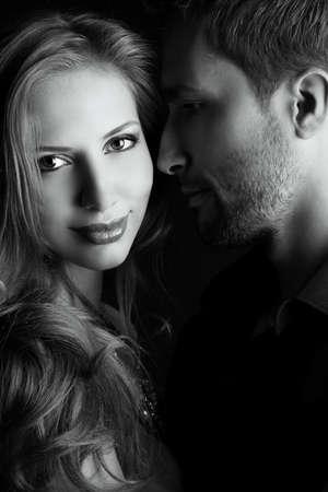 baiser amoureux: Portrait d'une belle jeune couple dans l'amour posant dans le studio sur sombre. Banque d'images
