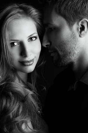 tender passion: Portrait of a beautiful young couple in love posing at studio over dark . Stock Photo