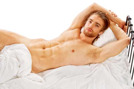 nudo maschile: Uomo bello che giace in un letto. Isolato su bianco.