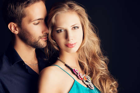 Portrait of a beautiful young couple in love posing at studio over dark . photo