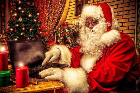 Santa Claus sitting at the table with a laptop at his home. Christmas time. photo