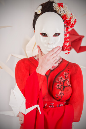Art portrait of a stylized Japanese geisha with mask. Body painting project. Stock Photo - 24130430