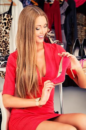 tienda zapatos: Muchacha de moda elegir zapatos en una tienda.