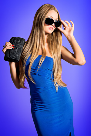 Portrait of a fashionable model in an evening dress and sunglasses. photo