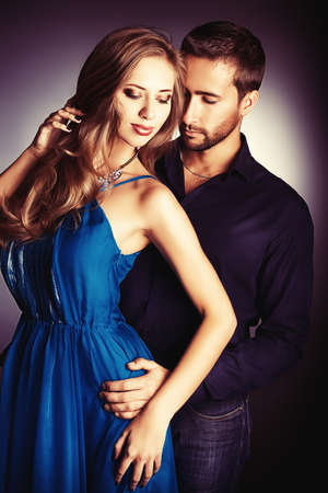 jovenes: Retrato de una pareja joven y bella en el amor que presenta en el estudio más oscuro.