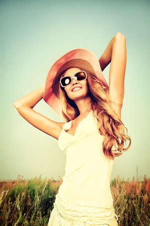 gafas de sol: Joven y bella mujer en elegante sombrero y gafas de sol posando sobre el cielo. Foto de archivo