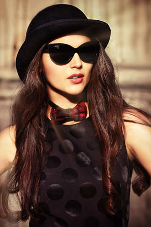 Beautiful brunette in bowler hat and bow-tie standing on the street of the old town. Retro style. photo