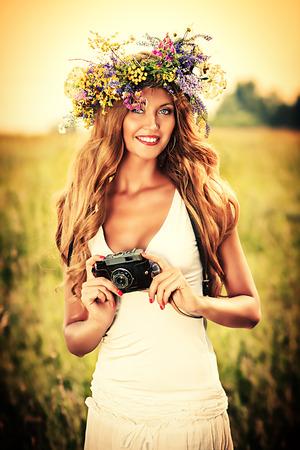 circlet: Ritratto di una romantica giovane donna sorridente in un cerchietto di fiori in piedi con la vecchia macchina fotografica all'aperto.