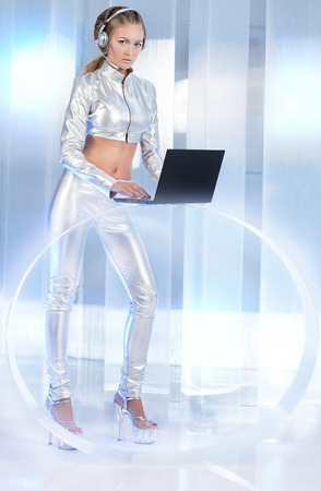 cyber woman: Beautiful young woman in silver latex costume with futuristic hairstyle and make-up working on a laptop. Sci-fi style.