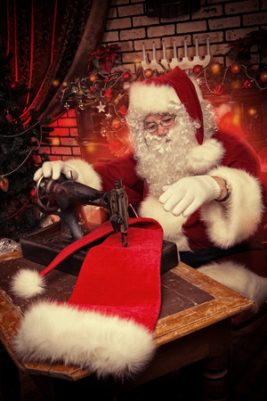 Santa Claus is sewing on a sewing machine cap for Christmas. photo