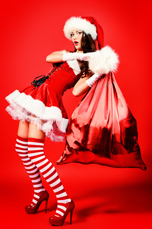 Beautiful young woman in Santa Claus costume holding big bag with presents over red background. Christmas. photo