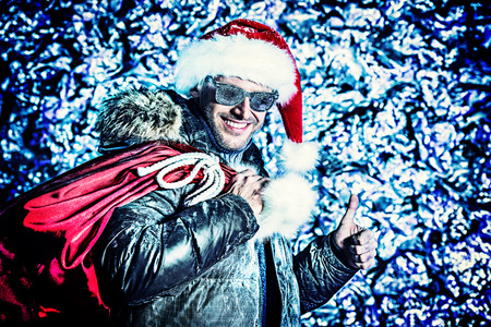 Handsome smiling man dressed in winter clothes and Santa Claus cap covered with frost. Christmas. photo
