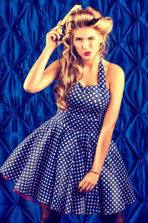 Charming pin-up woman with retro hairstyle and make-up posing with an old phone. Stock Photo - 24323712