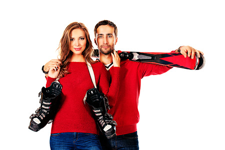 Two young people stand with skiing and ski boots. Winter sports. Isolated over white. photo