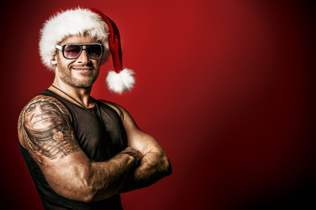 the tempter: Portrait of a handsome brutal man in Christmas hat. Over red background.