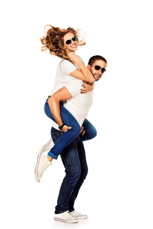 cute girlfriends: Happy young couple in love posing at studio. Isolated over white.