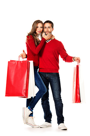 Happy young couple standing with a lot of shopping bags. Sale. Isolated over white. Stock Photo - 24323738