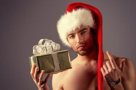 Sexual young man in Christmas hat holding a gift.  photo