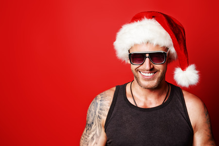 Portrait of a handsome brutal man in Christmas hat. Over red background. photo