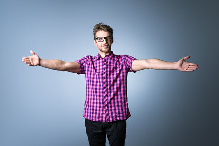 Modern young man in spectacles stands with arms outstretched to the sides.