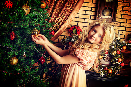 Cute little girl decorating Christmas tree at home. photo