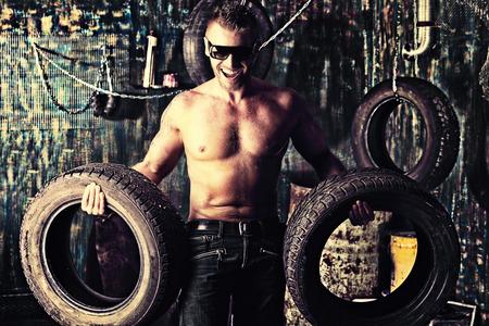 mecanica industrial: Hombre muscular hermoso en el antiguo garaje.
