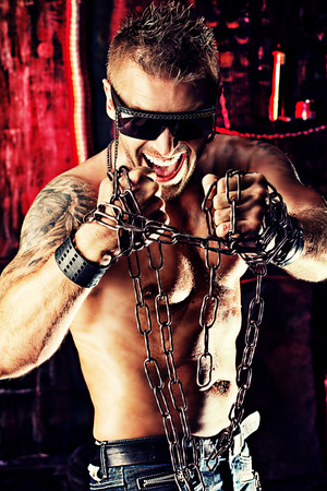 violence in the workplace: Handsome muscular man with chain in the old garage.