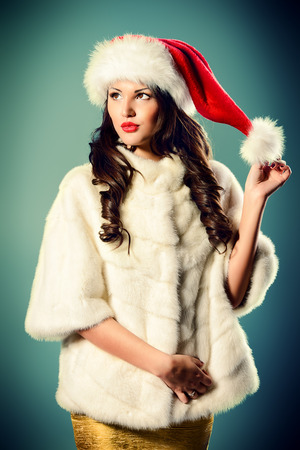 Gorgeous woman in white fur coat and Christmas hat posing at studio. photo