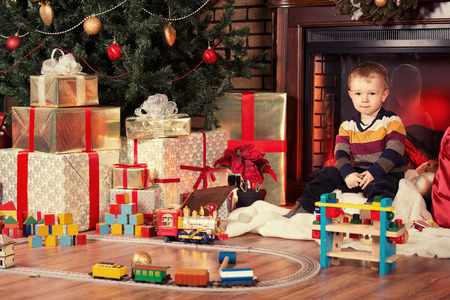 Little boy playing with toys at home near the fireplace and Christmas tree. Stock Photo - 24448228