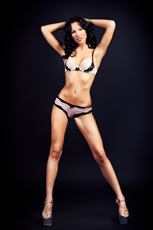 Full length portrait of a slender young woman in beautiful lingerie over black background. photo