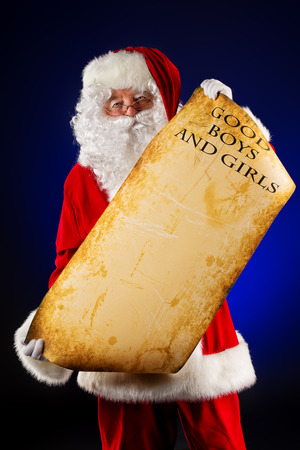 Santa Claus holds an old paper with a list of good boys and girls. Christmas. photo