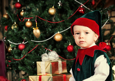 Portrait of a little boy dressed as an elf at home near the Christmas tree. photo
