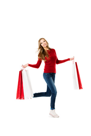 Happy young woman  running with a lot of shopping bags. Sale. Isolated over white. photo