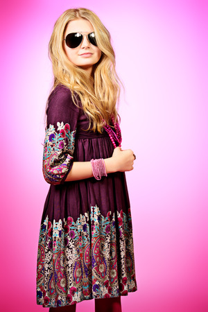 Little fashion girl in beautiful dress, beads and sunglasses posing over pink background.  photo