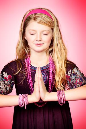 Little girl meditating over pink background.  photo