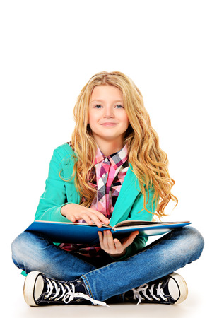 Cute ten years girl sitting with a book. Isolated over white.