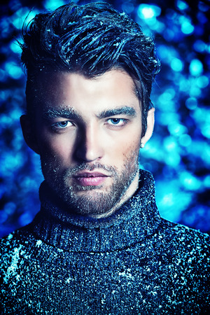 Portrait of a handsome man dressed in winter clothes, covered with frost and snow. photo