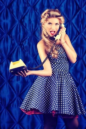 Charming pin-up woman with retro hairstyle and make-up talking on the phone. Stock Photo - 24679747