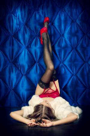 Seductive young woman in a sexual red lingerie and fur coat over vintage background. photo