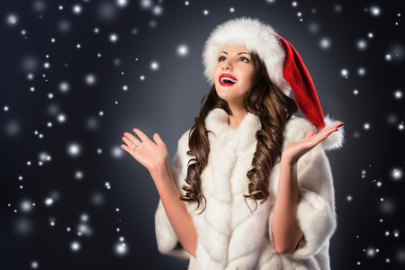 Happy beautiful woman in white fur coat and Christmas hat posing at studio. photo