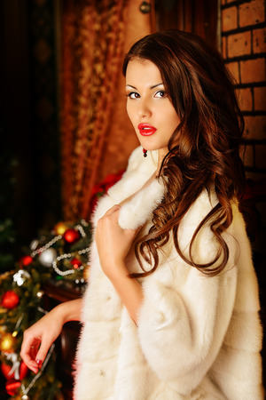 white fur: Mujer magn�fica en blanco posando abrigo de piel en las decoraciones de Navidad. Foto de archivo