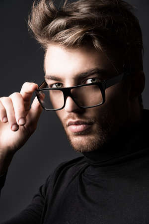 imposing: Portrait of an imposing man in elegant black clothes and glasses posing over dark background.