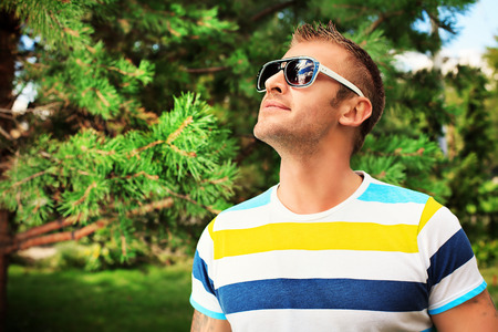 Smiling mature man in sunglasses standing outdoor and smiling. photo