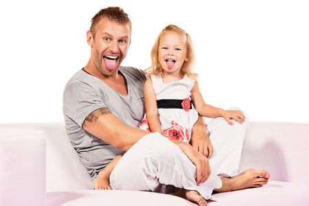 Happy father sitting with his little daughter on a sofa. Isolated over white. photo