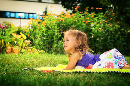 Happy little girl lying on a grass at the park. photo