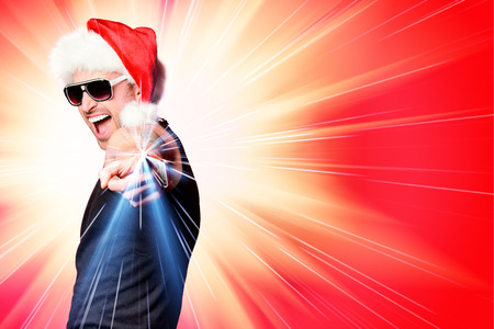 Portrait of a happy handsome brutal man in Christmas hat. Over red background. photo