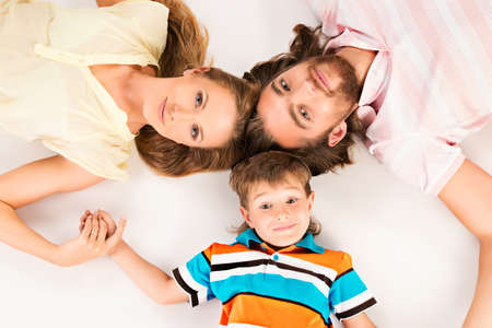 familia unida: Familia feliz que miente en la cabeza baja de la cabeza. Padre, madre e hijo. Aislado en blanco. Foto de archivo