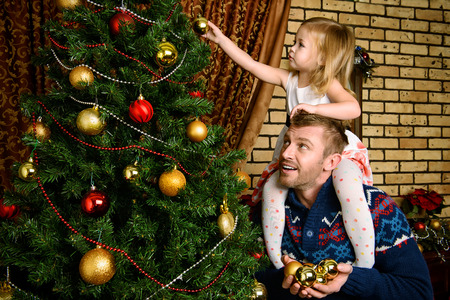 father daughter: Happy father and his little daughter decorating the Christmas tree at home. Stock Photo
