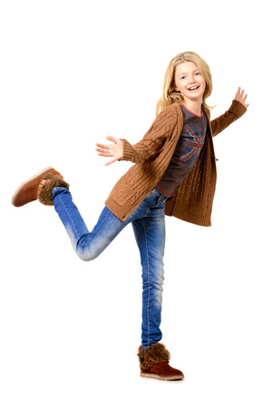 Portrait of a cheerful ten years girl jumping for joy. Isolated over white. photo