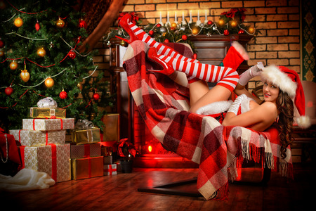Sexual young woman in Santa Claus costume posing in Christmas decorations. Stock Photo - 24760795
